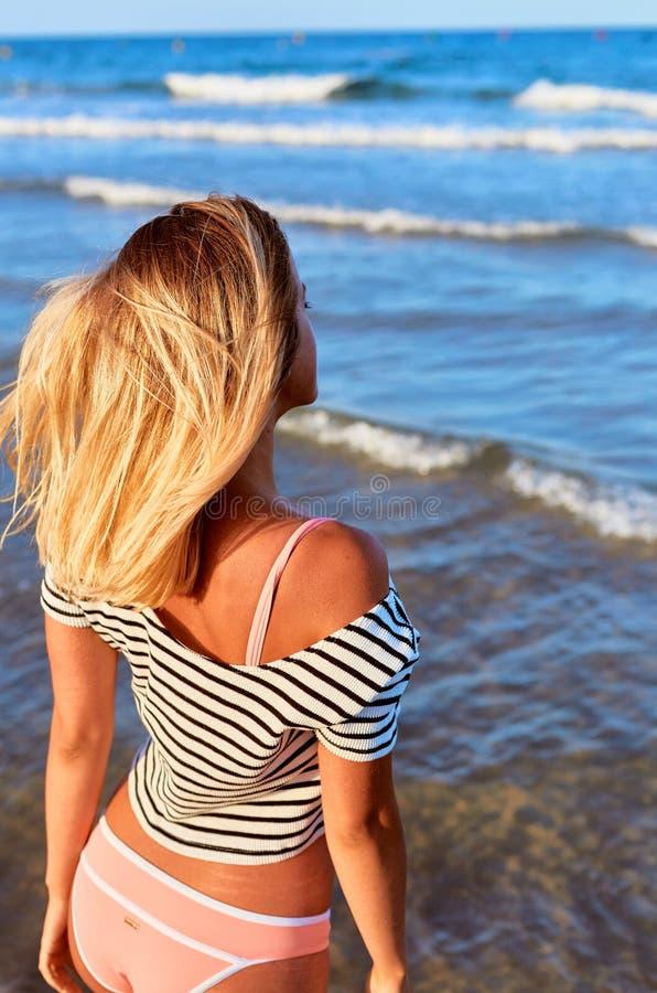 Jonge vrouw in zwempak in de zomer dichtbij het overzees en de blauwe hemel royalty-vrije stock foto