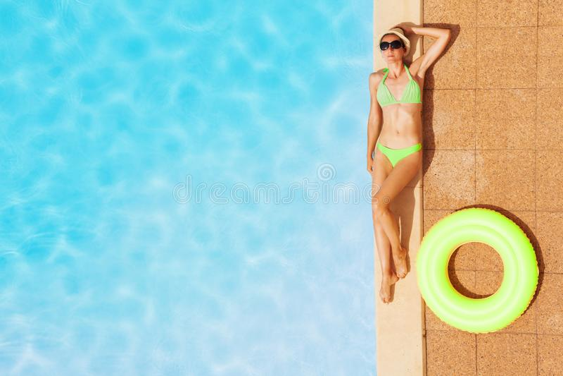 Jonge vrouw in zwempak het ontspannen door zwembad royalty-vrije stock foto