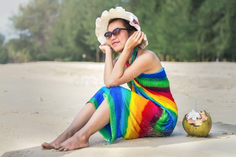 Jonge vrouw in zwempak met kokosnotencocktail stock afbeelding