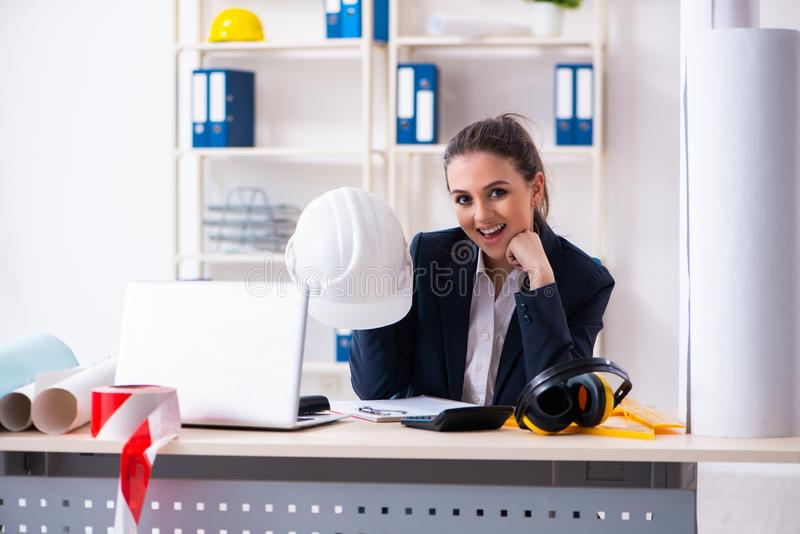 Jonge vrouwelijke architect die in het bureau werken stock afbeelding