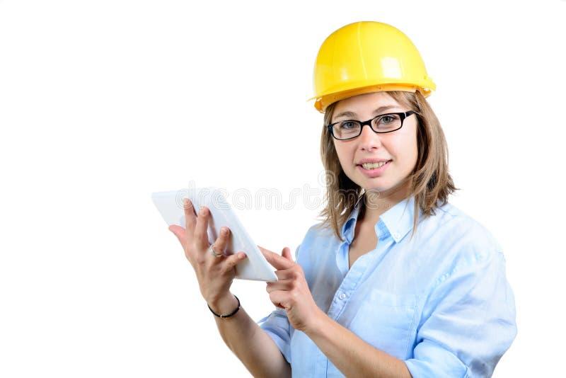 Jonge vrouwelijke architect met een gele helm en een digitale tablet royalty-vrije stock foto's