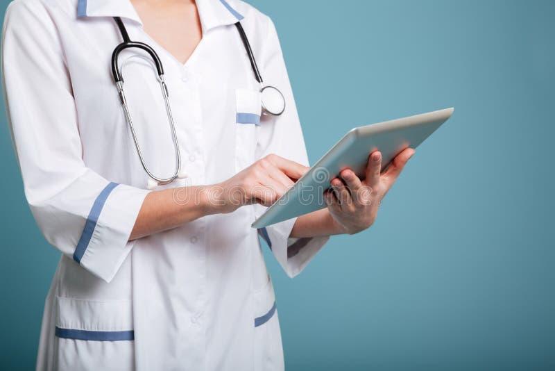 Jonge vrouwelijke arts die de eenvormige tablet van holdingspc dragen stock foto's