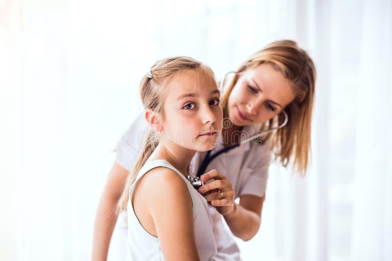 Jonge vrouwelijke arts die een klein meisje in haar bureau onderzoeken royalty-vrije stock fotografie