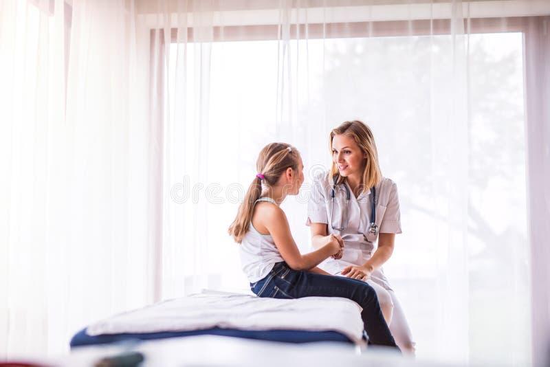 Jonge vrouwelijke arts en een klein meisje in haar bureau royalty-vrije stock foto