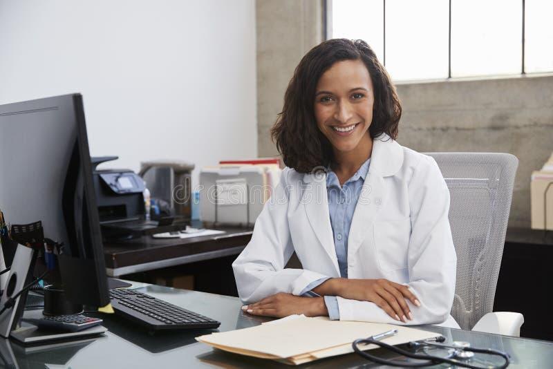 Jonge vrouwelijke artsenzitting bij bureau in een bureau, portret stock afbeelding