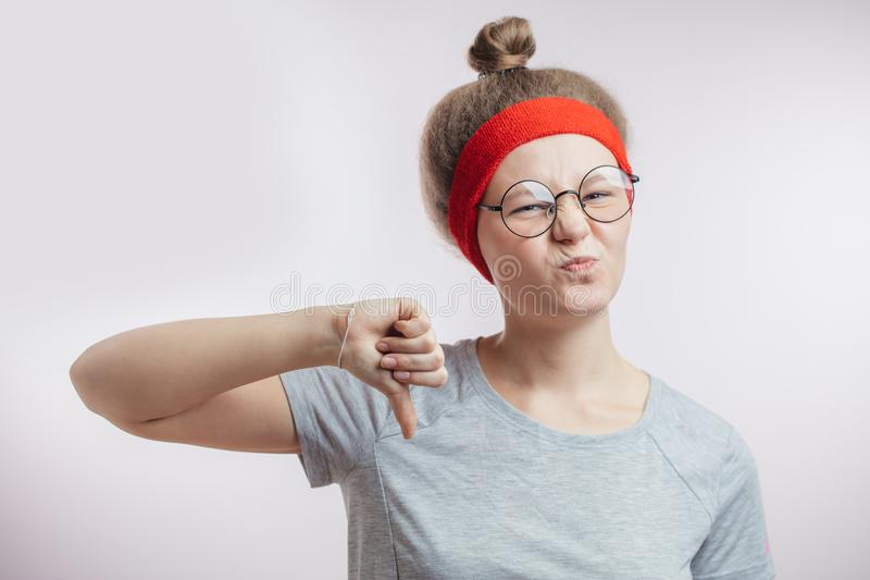 Jonge vrouwelijke atleet die een negatief gebaar tonen yuk druk afkeer uit stock afbeelding