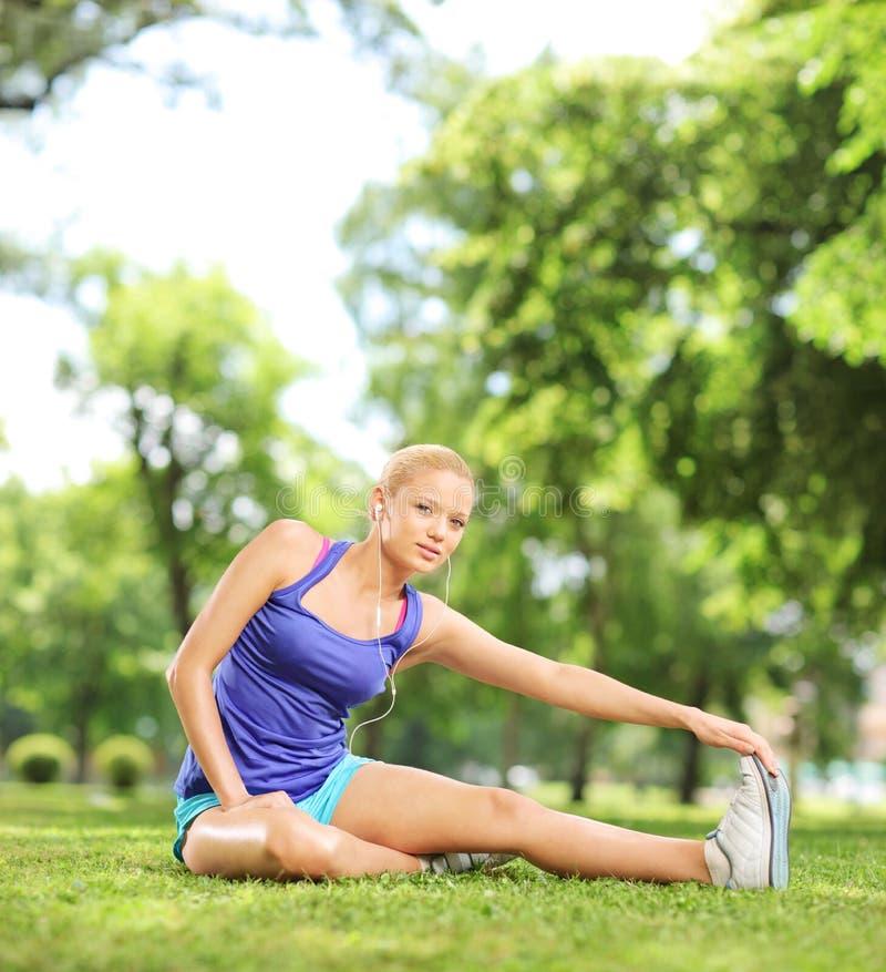 Jonge vrouwelijke atleet die haar been in een park uitrekken stock foto