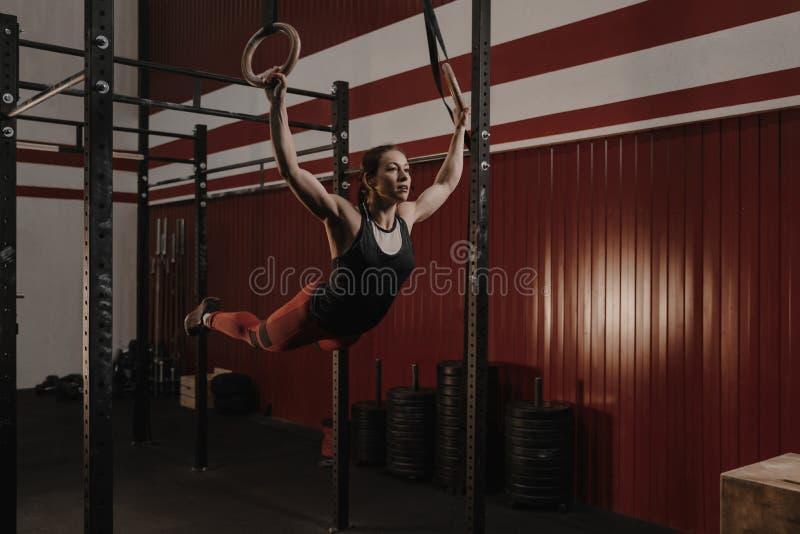 Jonge vrouwelijke atleet die op gymnastiek- ringen bij crossfitgymnastiek slingeren stock fotografie