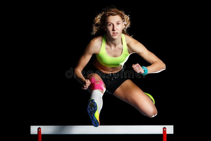 Jonge vrouwelijke atleet die over hindernis in sprint springen stock fotografie