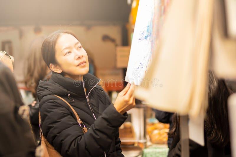 Jonge vrouwelijke Aziatische toeristenvrouw die en kleren op straatmarkt winkelen kiezen stock fotografie