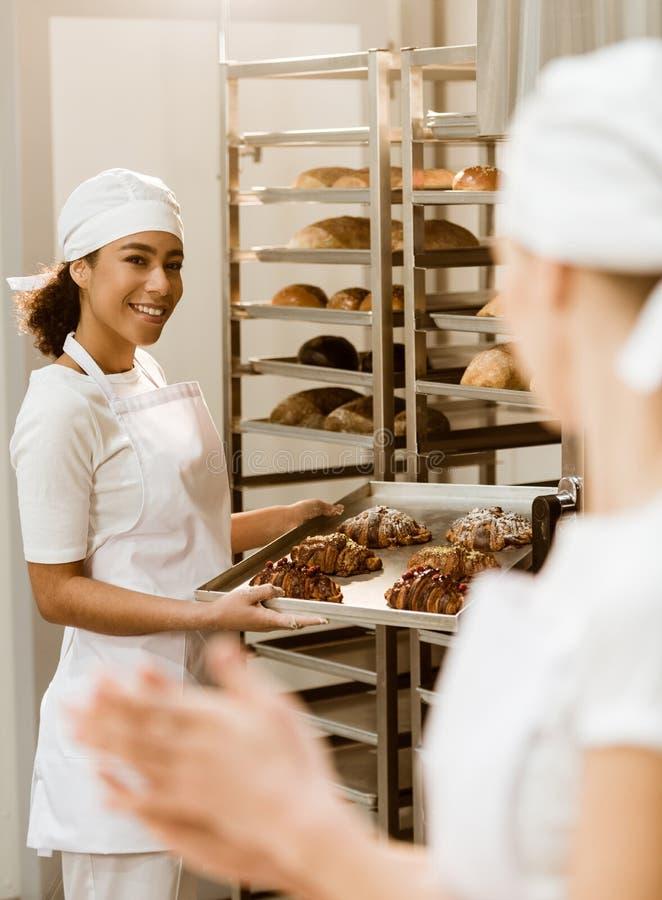 jonge vrouwelijke bakkers die bij bakselvervaardiging samenwerken royalty-vrije stock foto