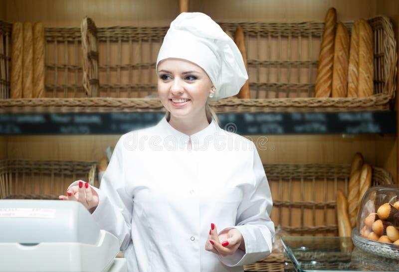 Jonge vrouwelijke bakkers die met gebakje in bakkerij glimlachen royalty-vrije stock fotografie