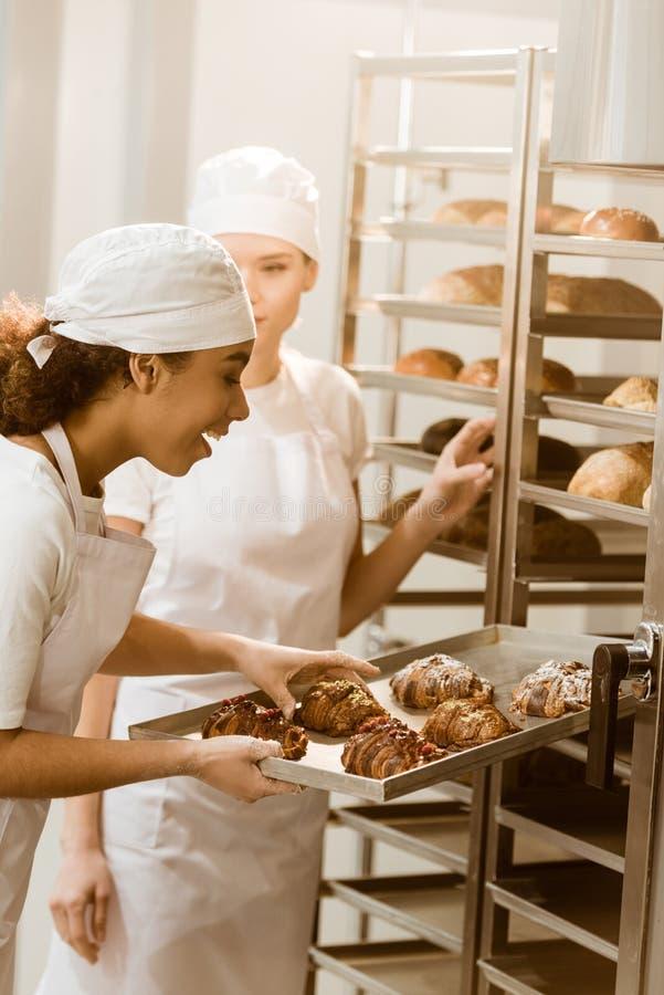 jonge vrouwelijke bakkers die vers gebakje op planken zetten royalty-vrije stock fotografie