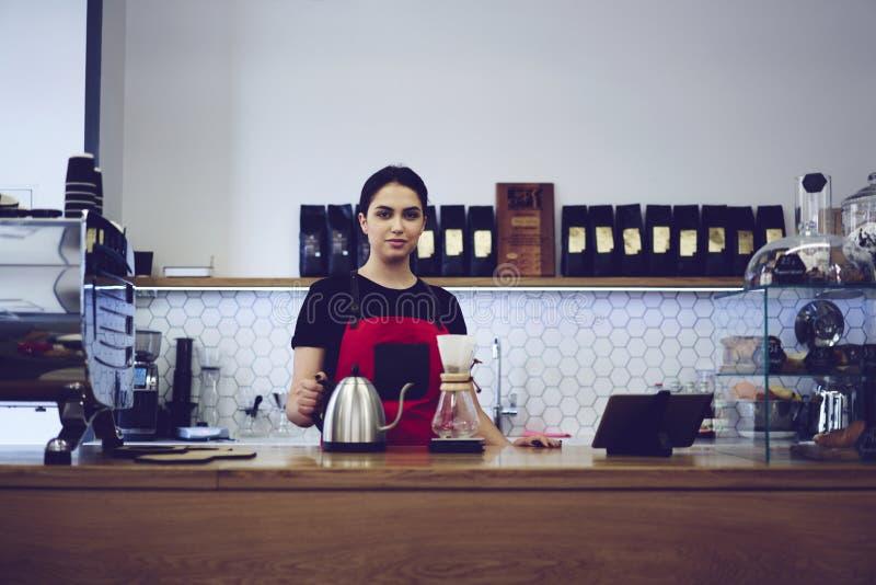 Jonge vrouwelijke barista die gefiltreerde koffiedrank maken die speciale technologie gebruiken royalty-vrije stock fotografie