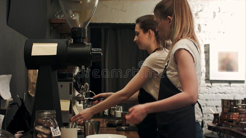 Jonge vrouwelijke barista twee die in koffiewinkel werken, pareparing koffie royalty-vrije stock foto