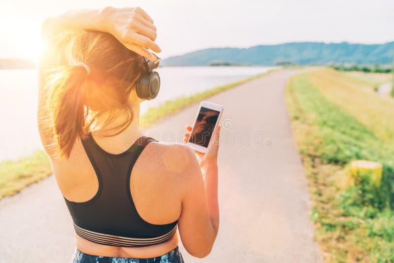 Jonge vrouwelijke beginnende jogging en het luisteren aan muziek die smartphone en draadloze hoofdtelefoons met behulp van royalty-vrije stock afbeeldingen
