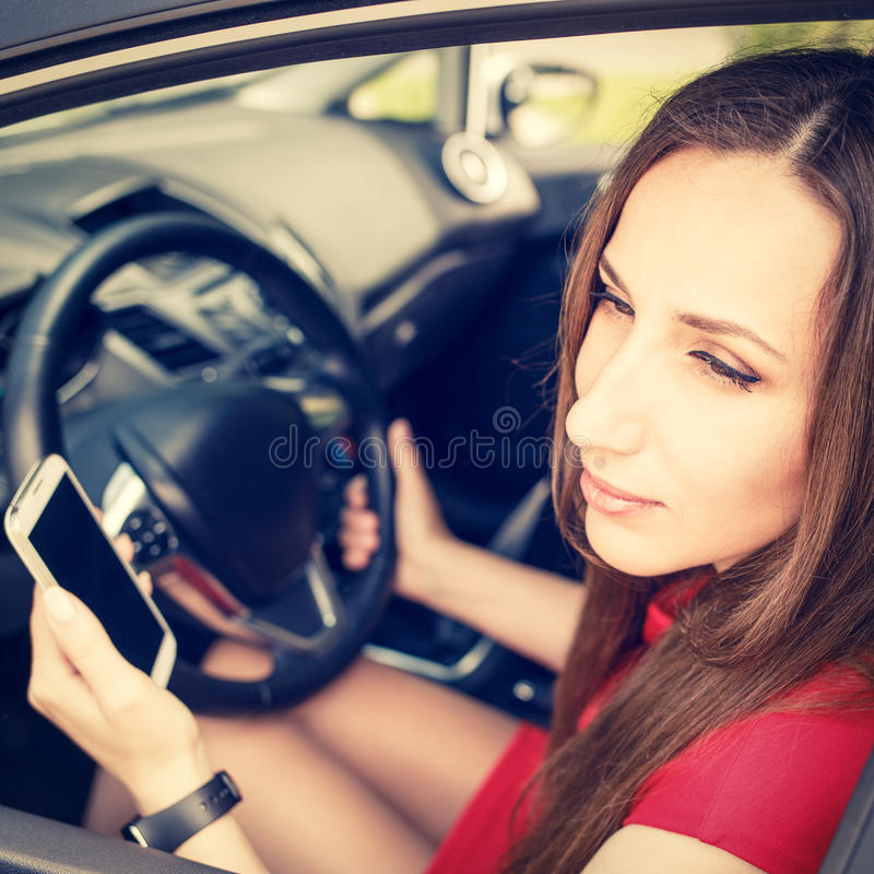 Jonge vrouwelijke bestuurder die smartphone in auto gebruiken stock foto