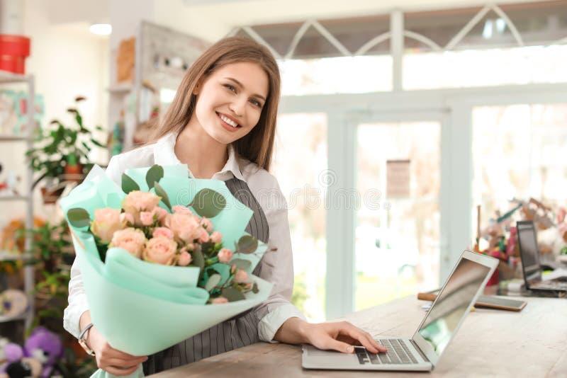 Jonge vrouwelijke bloemist met boeket en laptop die in bloemwinkel werken royalty-vrije stock foto's