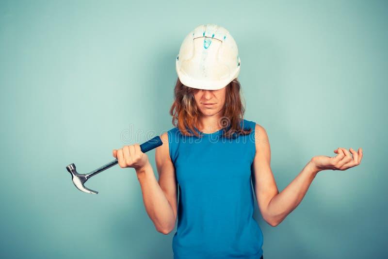 Jonge vrouwelijke bouwer met hamer stock foto