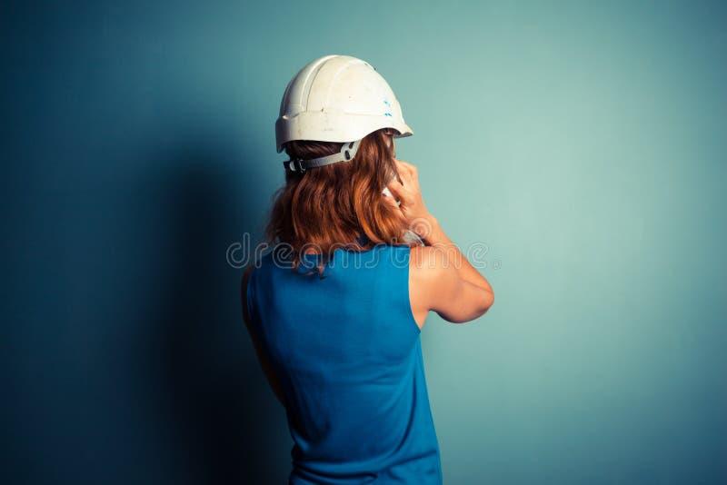 Jonge vrouwelijke bouwer op de telefoon royalty-vrije stock afbeelding