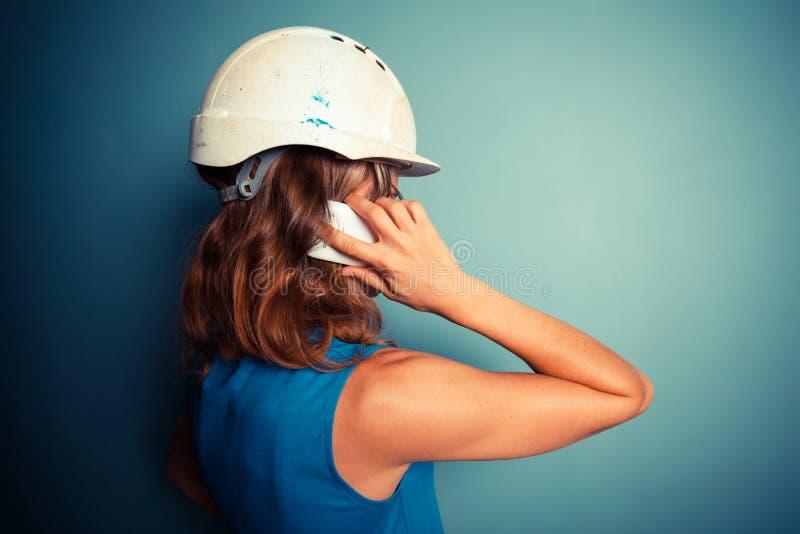 Jonge vrouwelijke bouwer op de telefoon stock foto's