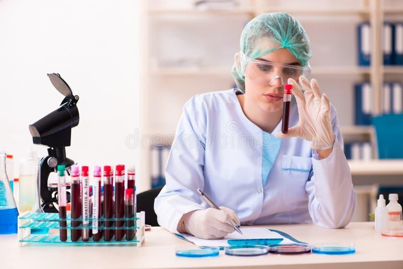 Jonge vrouwelijke chemicus die in het laboratorium werken stock foto