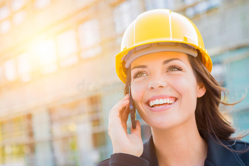 Jonge Vrouwelijke Contractant die Bouwvakker op Plaats dragen die Telefoon met behulp van stock foto