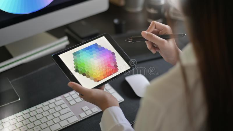 Jonge vrouwelijke creatieve kunstenaar van Webontwerp met het werken aan kleurenselectie op grafische tablet stock foto's