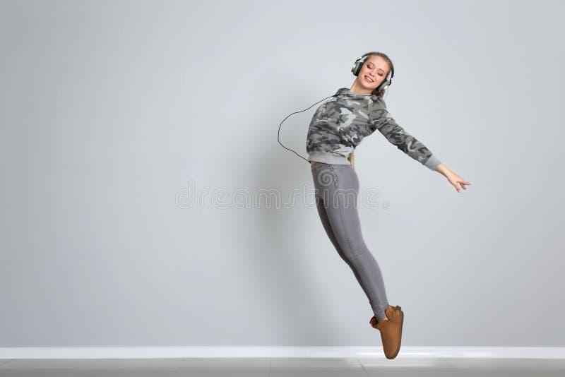 Jonge vrouwelijke danser tegen witte muur stock foto