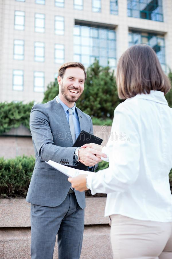 Jonge vrouwelijke en mannelijke bedrijfsmensen die handen na een succesvolle vergadering voor een bureaugebouw schudden stock foto