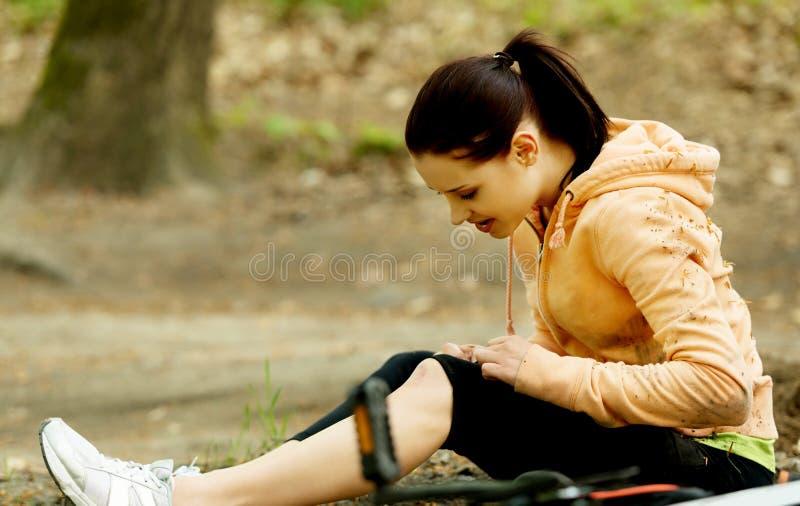 Jonge vrouwelijke fietser met gekwetst been royalty-vrije stock foto's