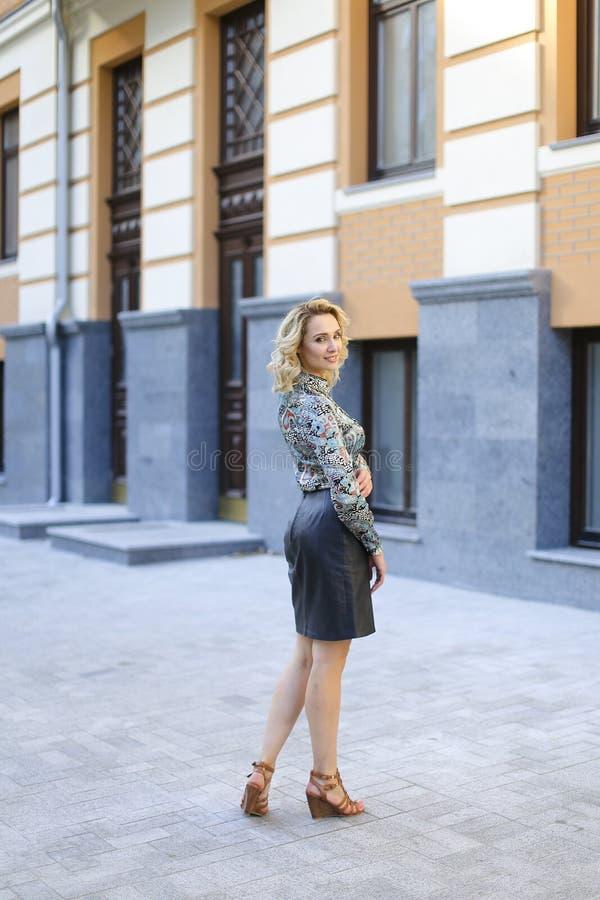 Jonge vrouwelijke foto model status dichtbij het inbouwen van achtergrond en het dragen van leerrok royalty-vrije stock afbeelding