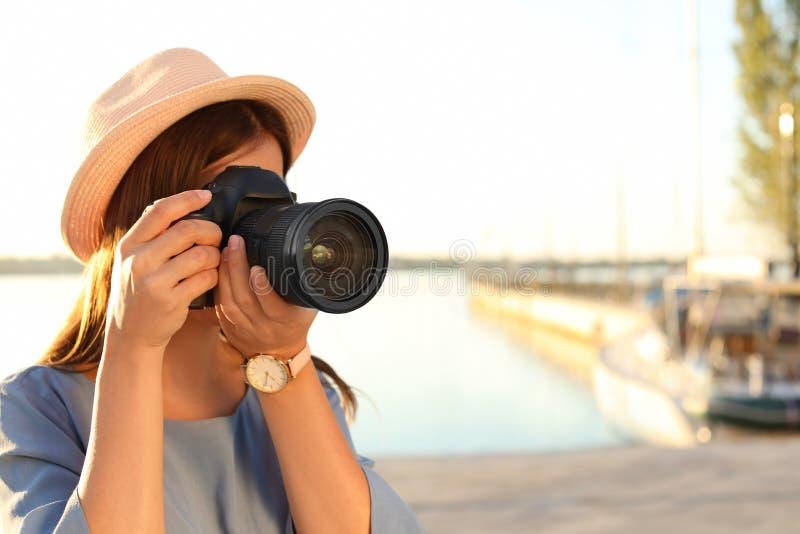 Jonge vrouwelijke fotograaf die foto met professionele camera nemen bij pijler stock foto's