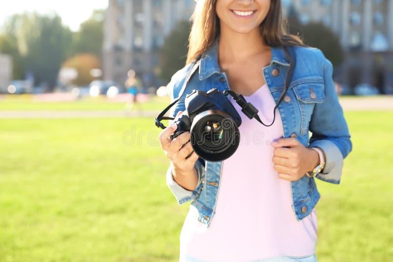 Jonge vrouwelijke fotograaf die professionele camera op straat houden stock afbeelding