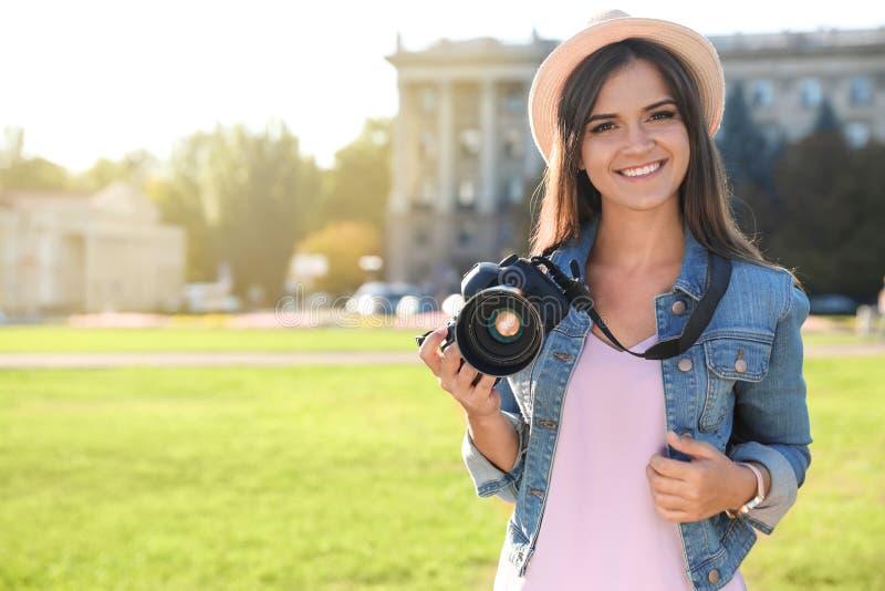 Jonge vrouwelijke fotograaf die professionele camera op straat houden royalty-vrije stock afbeelding