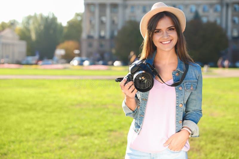 Jonge vrouwelijke fotograaf die professionele camera op straat houden royalty-vrije stock fotografie