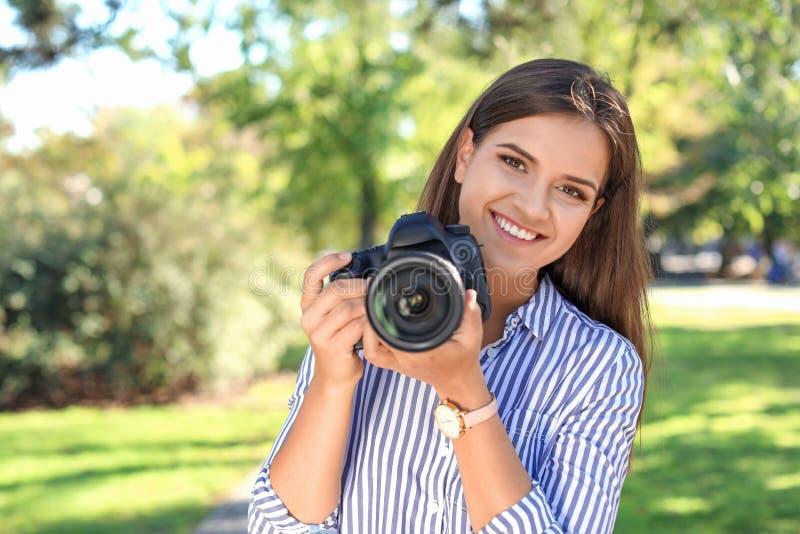 Jonge vrouwelijke fotograaf met professionele camera stock fotografie