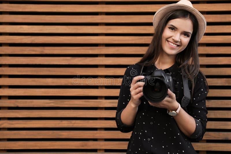 Jonge vrouwelijke fotograaf met professionele camera dichtbij houten muur royalty-vrije stock foto's