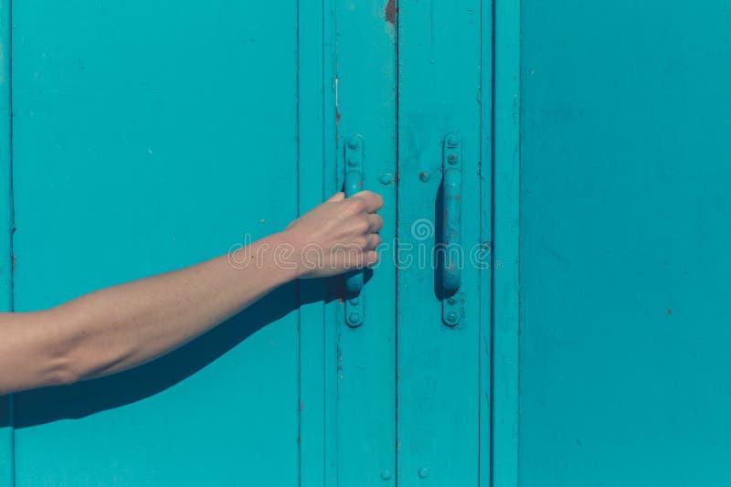 Jonge vrouwelijke hand die blauwe deur grijpen royalty-vrije stock foto's