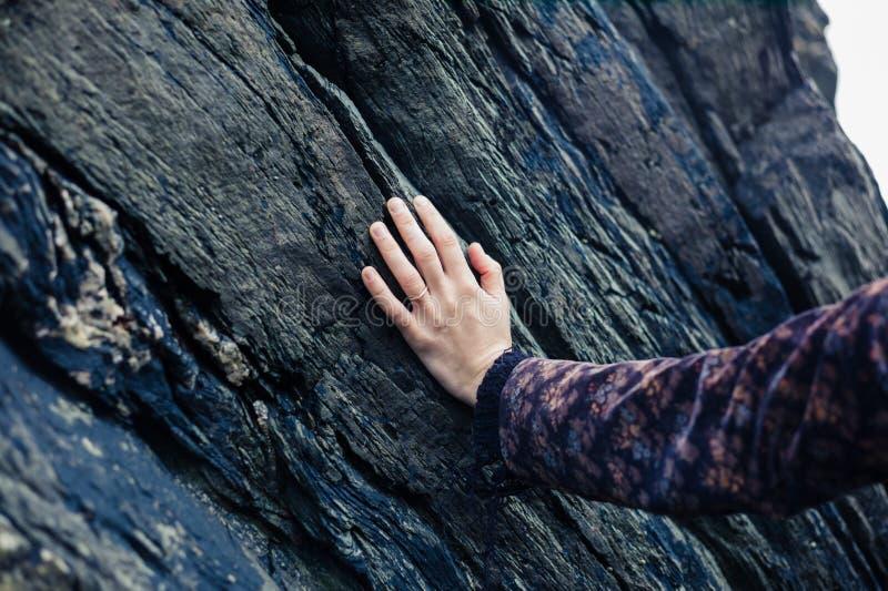 Jonge vrouwelijke hand wat betreft rots stock fotografie