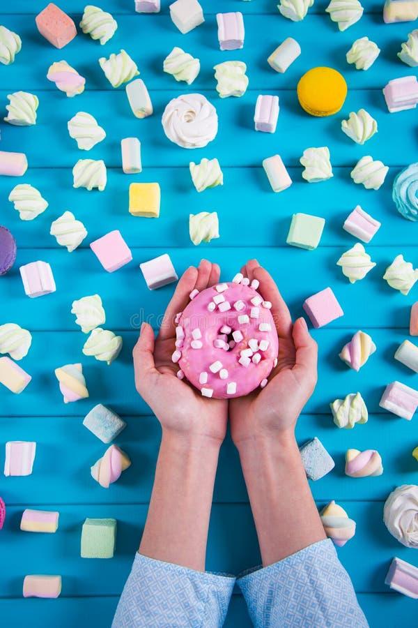 Jonge vrouwelijke handen die één roze doughnut met heel wat vierkante kleurrijke heemst op blauwe achtergrond houden royalty-vrije stock fotografie