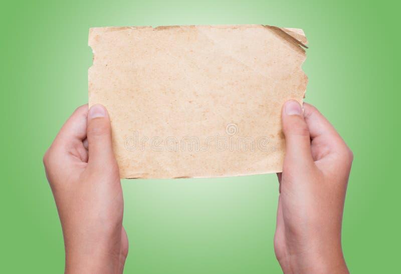 Jonge vrouwelijke handen die uitstekend document blad over groene backgr houden royalty-vrije stock fotografie
