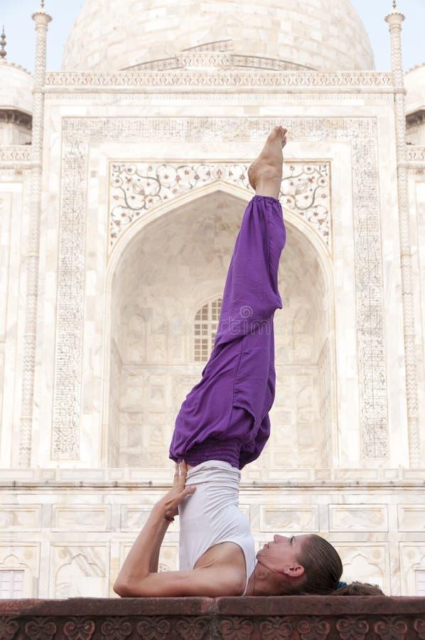 Jonge vrouwelijke het praktizeren yogaasana Sarvangasana in Taj Mahal stock fotografie
