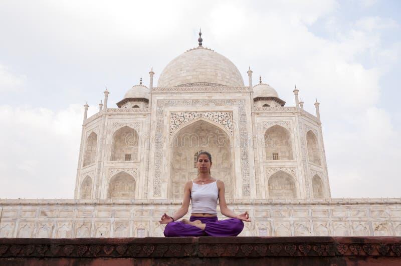 Jonge vrouwelijke het praktizeren yogameditatie in Taj Mahal stock afbeelding