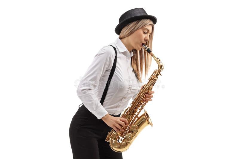Jonge vrouwelijke jazzmusicus die een saxofoon spelen stock afbeelding