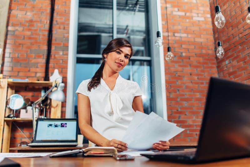 Jonge vrouwelijke journalist die documenten voorbereiden die van een de nieuwe artikelholding laptop zitting gebruiken bij bureau royalty-vrije stock afbeelding