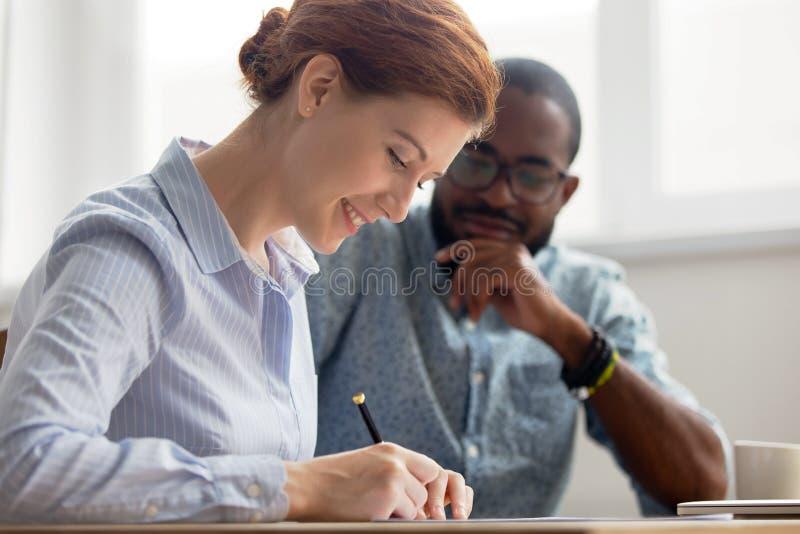 Jonge vrouwelijke kandidaat die contract na succesvol gesprek in bureau ondertekent royalty-vrije stock afbeelding