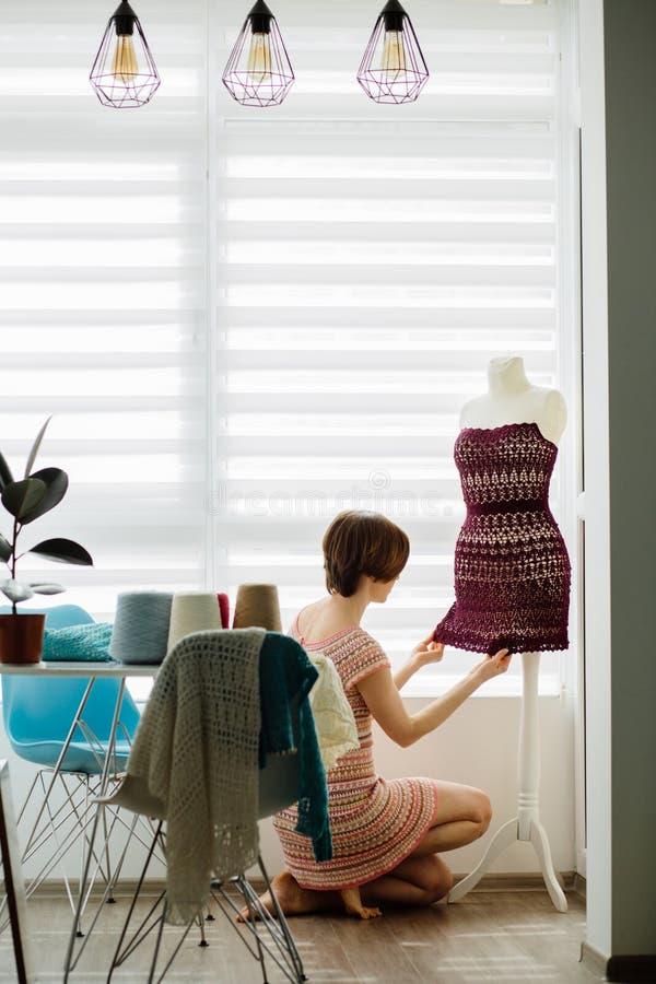Jonge vrouwelijke kledingsontwerper die kledingsmodel gebruiken bij comfortabele huis binnenlandse, freelance levensstijl Vertica stock afbeeldingen