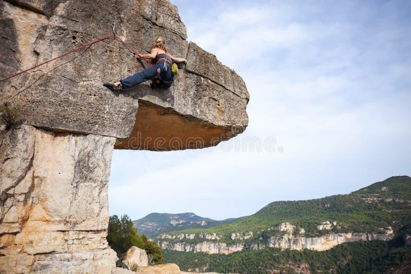Jonge vrouwelijke klimmer op een klip stock foto's