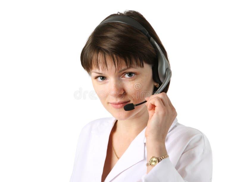 Jonge vrouwelijke kliniekreceptionnist die hoofdtelefoon draagt royalty-vrije stock foto's